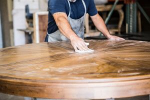 person wiping on finish on round wood table